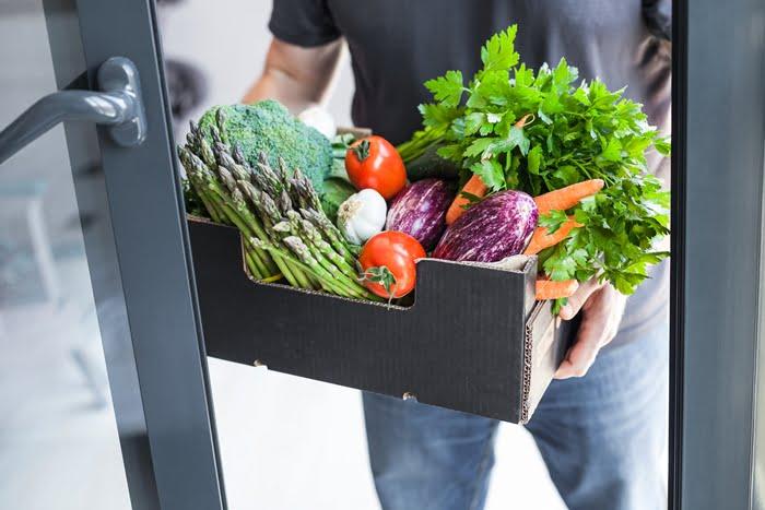 Vendedor com verduras de porta em porta